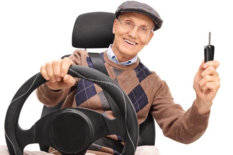 Homem superior que conduz e que guarda uma chave do carro imagens de stock royalty free