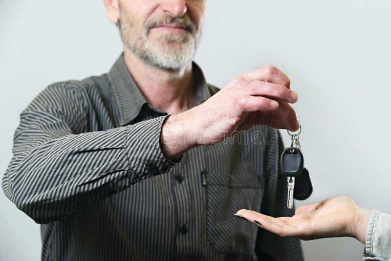Homem superior que dá a chave do carro fotografia de stock royalty free