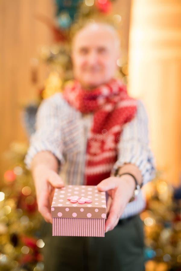 Homem superior que dá o presente à câmera imagens de stock