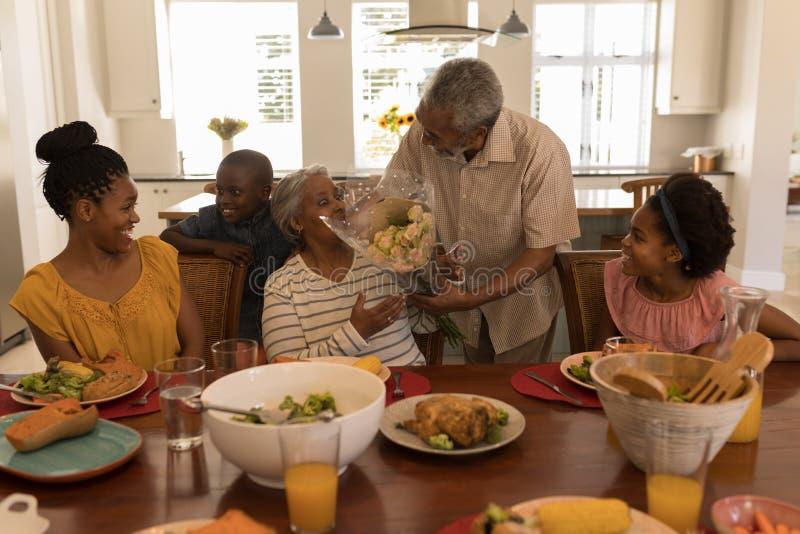 Homem superior que dá o ramalhete da flor à mulher superior na mesa de jantar imagens de stock