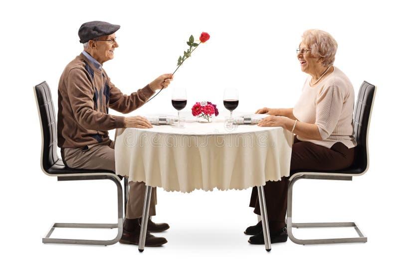 Homem superior que dá uma rosa vermelha a uma mulher superior em uma tabela do restaurante imagens de stock