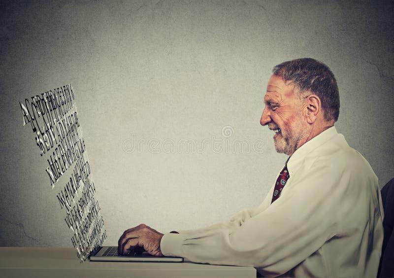 Homem superior que datilografa em seu laptop com a tela feita de letras do alfabeto imagens de stock
