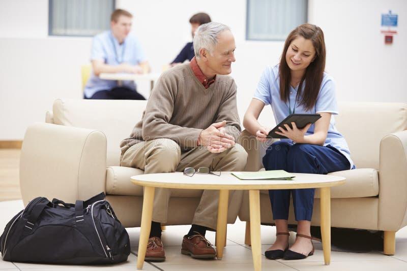Homem superior que discute resultados com a enfermeira On Digital Tablet fotografia de stock