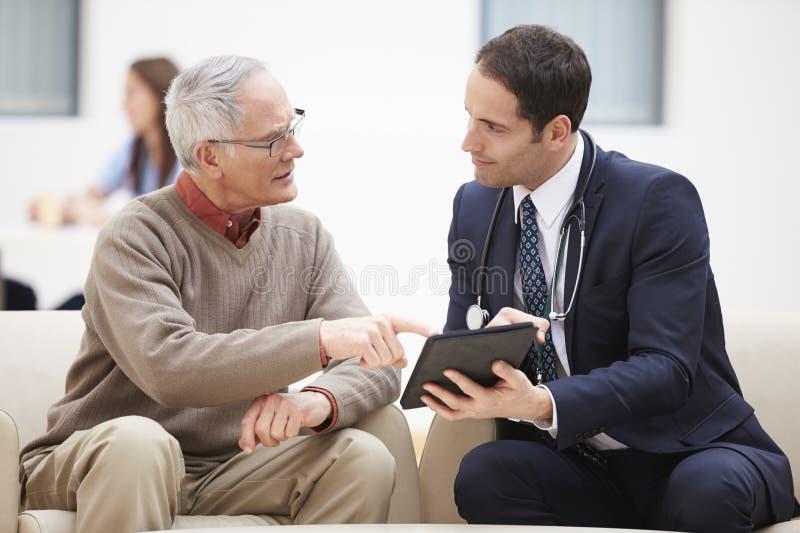 Homem superior que discute resultados com o doutor On Digital Tablet fotografia de stock