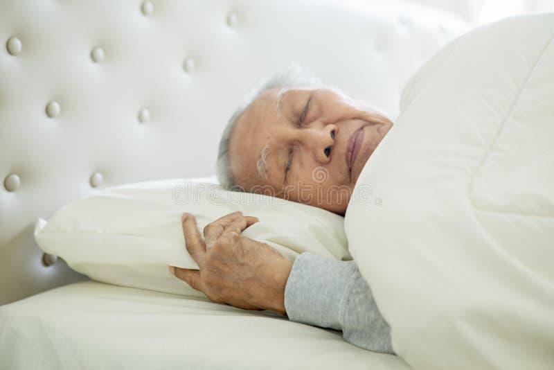 Homem superior que dorme bem na cama imagens de stock