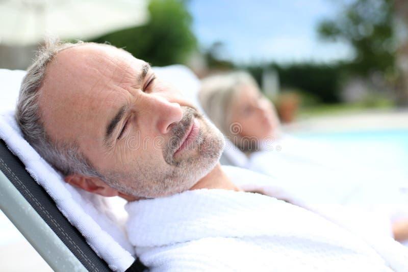 Homem superior que dorme na cadeira longa imagens de stock royalty free