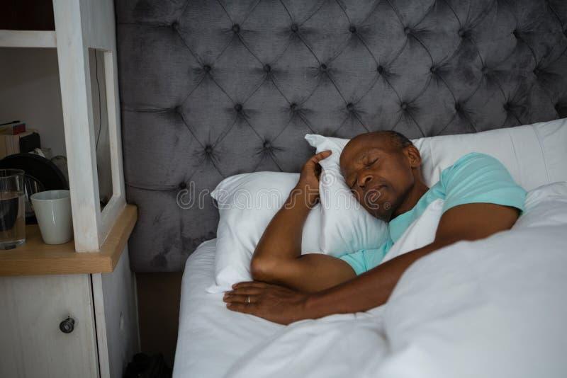 Homem superior que dorme na cama em casa fotografia de stock royalty free