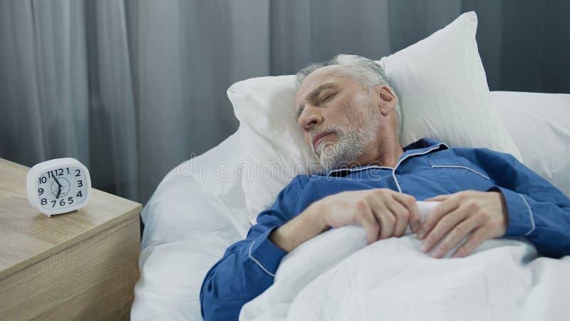 Homem superior que dorme na cama na manhã, resto saudável durante o tempo de recuperação imagem de stock royalty free