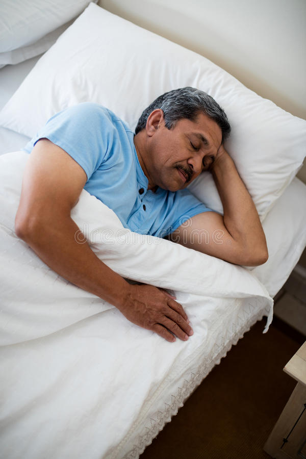 Homem superior que dorme na cama no quarto imagem de stock royalty free