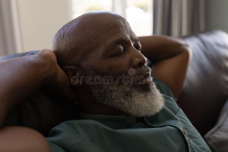 Homem superior que dorme na sala de visitas imagens de stock