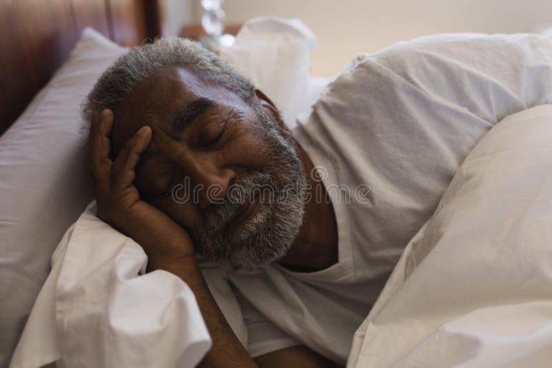 Homem superior que dorme no quarto em casa imagens de stock