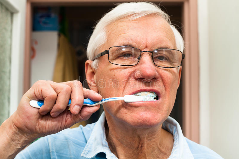 Homem superior que escova seus dentes foto de stock royalty free