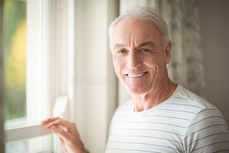 Homem superior que está pela janela foto de stock royalty free