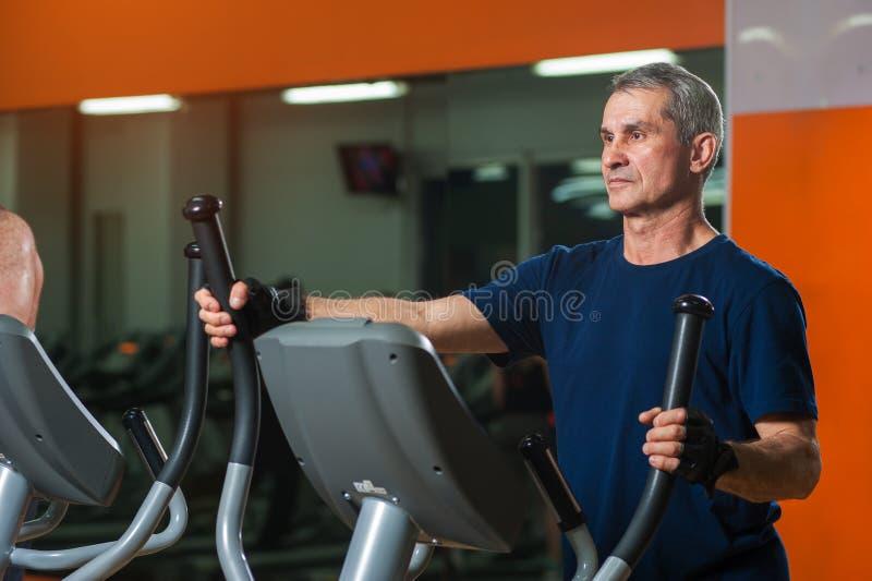 Homem superior que exercita na máquina elíptica no gym fotografia de stock royalty free