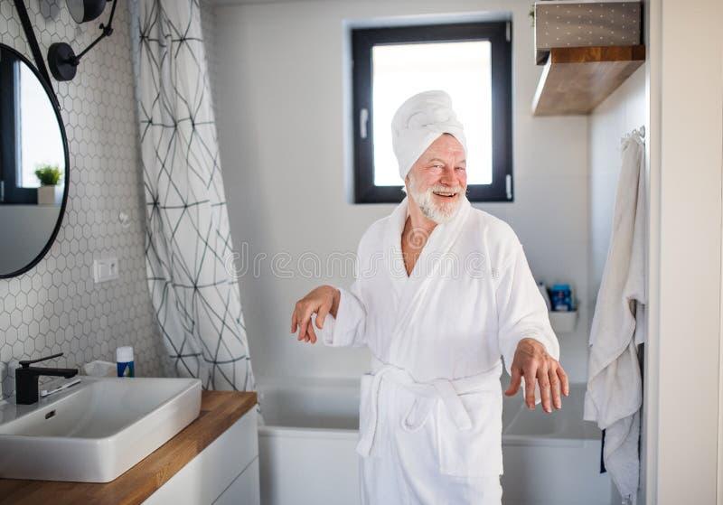 Homem superior que faz a rotina da manhã no banheiro dentro em casa imagens de stock