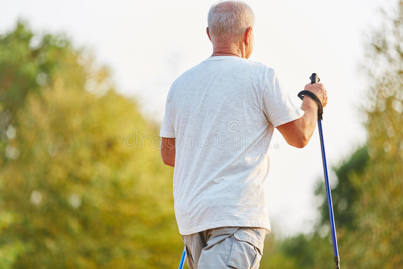Homem superior que faz uma caminhada nórdica para a reabilitação imagem de stock
