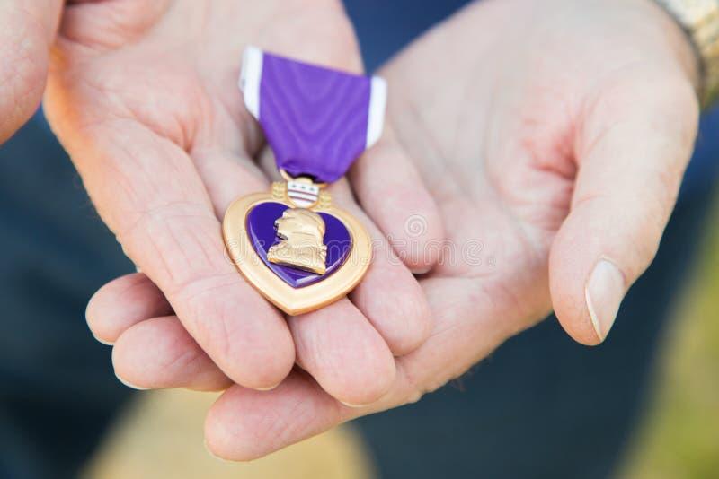 Homem superior que guarda a medalha militar de Purple Heart em suas mãos imagem de stock royalty free