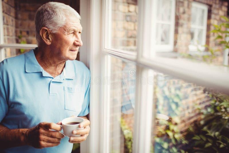 Homem superior que guarda o copo e que olha fora da janela fotografia de stock