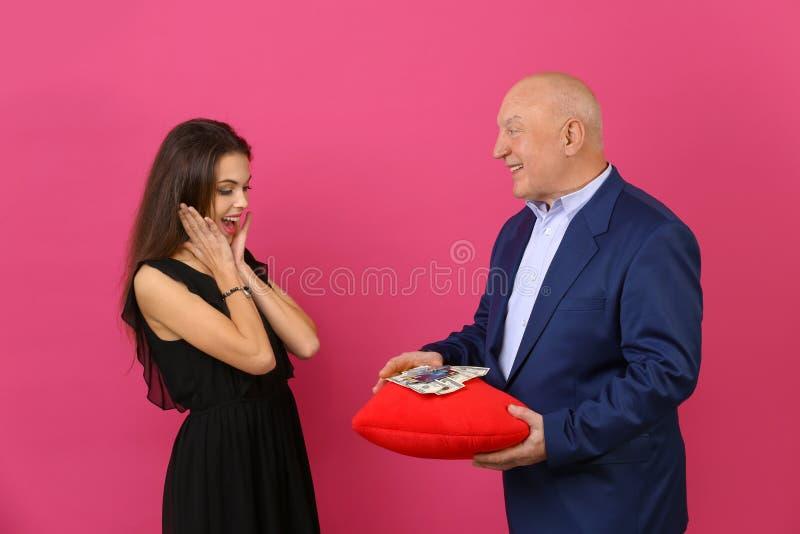 Homem superior que guarda o coração vermelho com dinheiro e jovem mulher no fundo da cor Uni?o de conveni?ncia imagens de stock