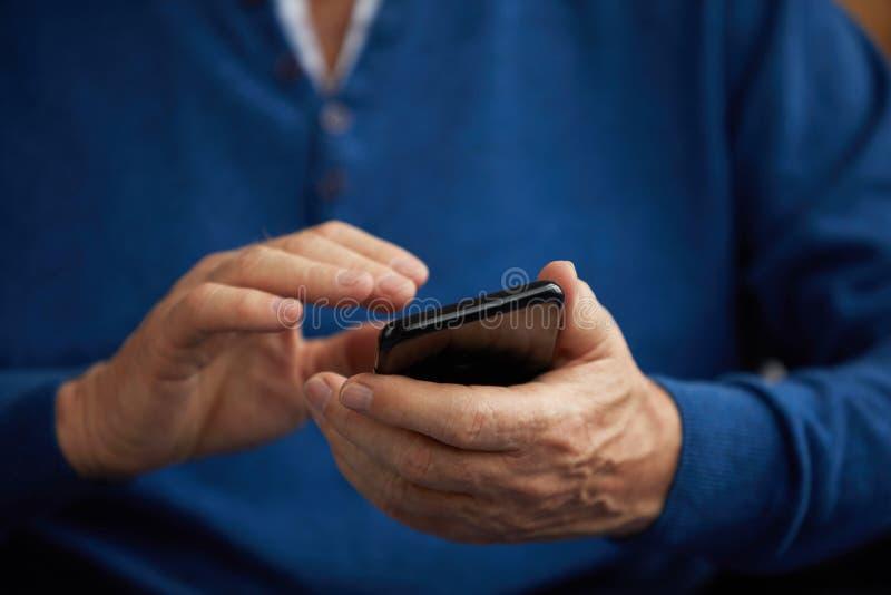 Homem superior que guarda Smartphone fotos de stock royalty free
