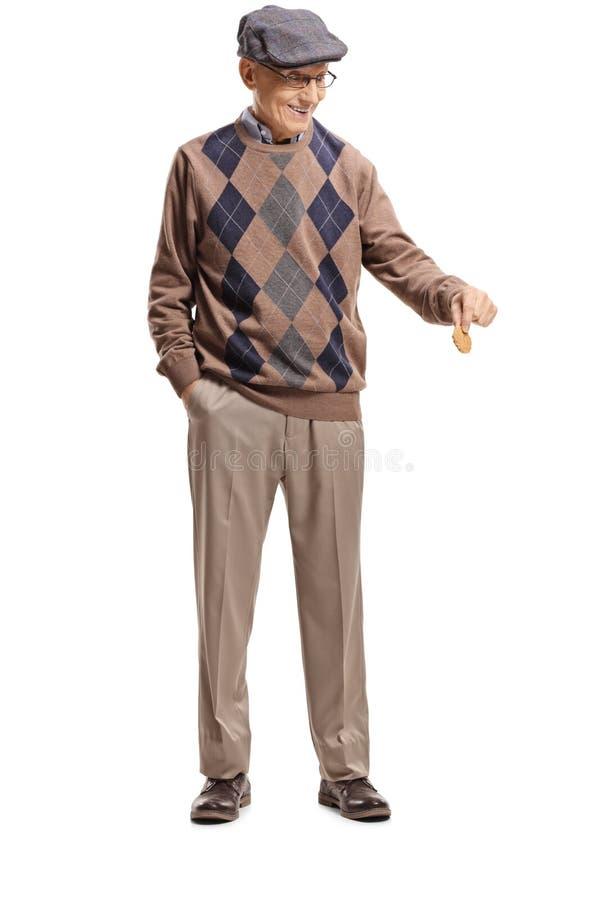 Homem superior que guarda um biscoito e que olha para baixo foto de stock