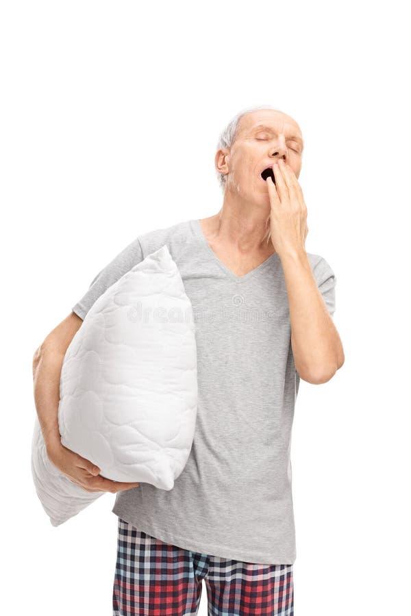 Homem superior que guarda um descanso e que boceja imagens de stock