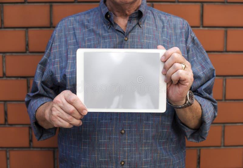 Homem superior que guarda uma tabuleta digital imagem de stock