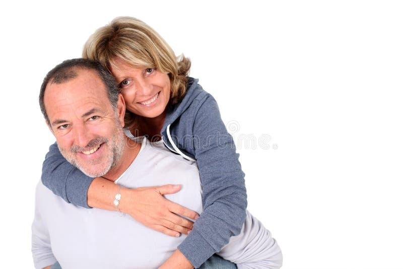 Homem superior que leva sua esposa no seu para trás fotos de stock