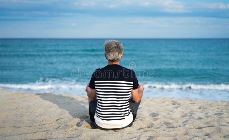 Homem superior que medita sobre a praia imagem de stock royalty free