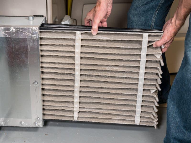 Homem superior que muda um filtro de ar sujo em uma fornalha da ATAC imagens de stock