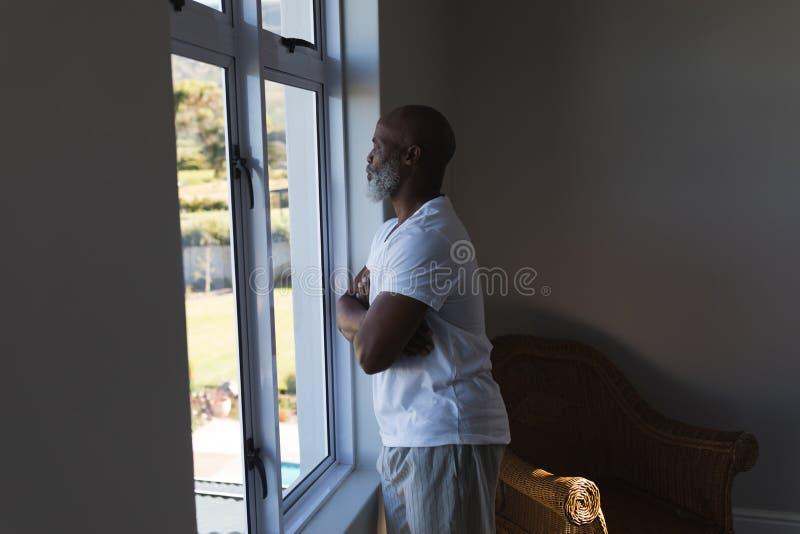Homem superior que olha através da janela em casa foto de stock