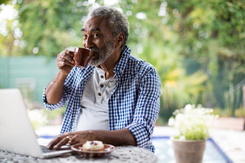 Homem superior que olha ausente ao beber o café fotografia de stock