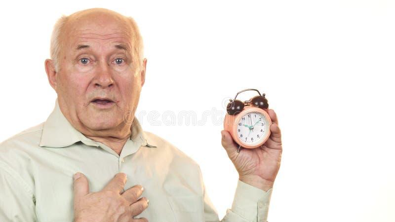 Homem superior que olha chocado verificando o tempo no despertador imagens de stock royalty free