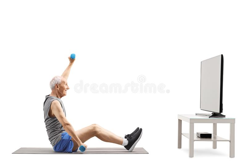 Homem superior que olha a tevê e que exercita em casa com pesos foto de stock royalty free