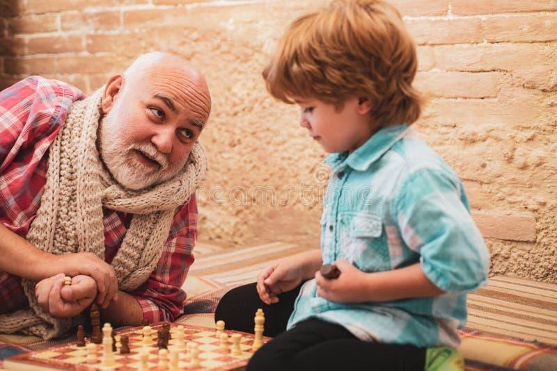 Homem superior que pensa sobre seu pr?ximo passo em um jogo de xadrez Av? e neto que jogam a xadrez Jogo de primeira gera??o fotos de stock royalty free