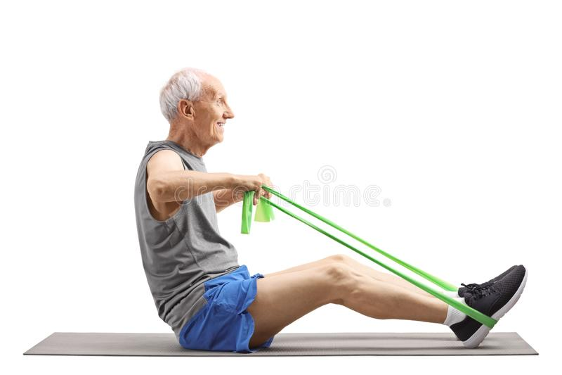 Homem superior que senta-se e que exercita com uma faixa elástica imagem de stock royalty free