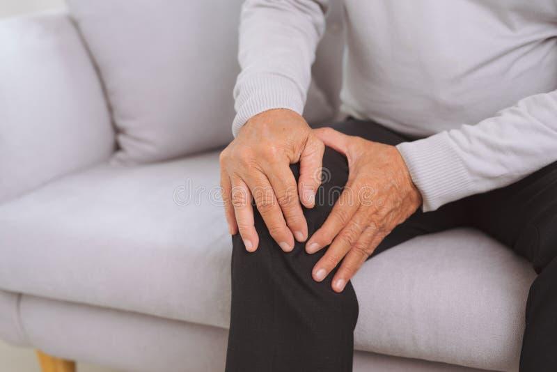 Homem superior que senta-se em um sofá na sala de visitas em casa e que toca em seu joelho pela dor fotos de stock royalty free