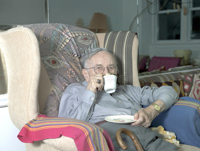 Homem superior que senta-se no sofá com beber do copo foto de stock