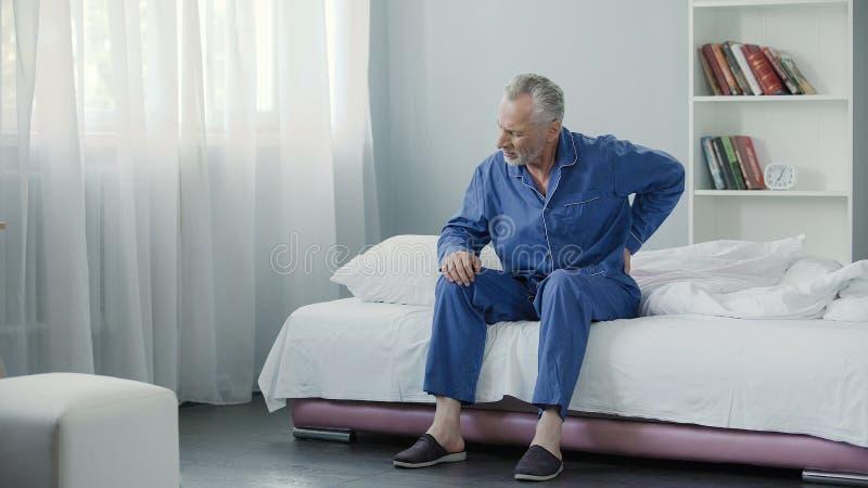 Homem superior que sofre a dor nas costas afiada, pessoa doente que levanta-se da cama, manhã imagem de stock royalty free