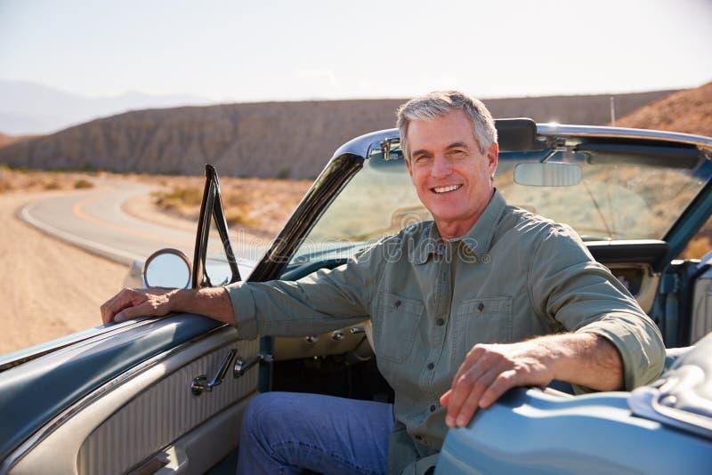 Homem superior que sorri à câmera do carro superior aberto estacionado foto de stock
