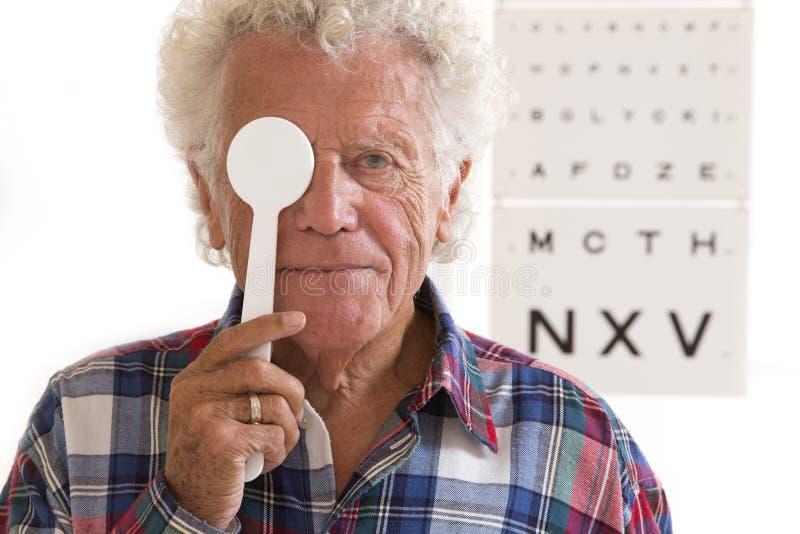 Homem superior que tem o exame da oftalmologia fotografia de stock