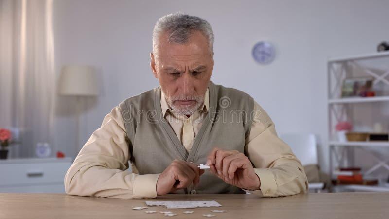 Homem superior que tenta recolher o enigma, problemas de memória, prejuízo cognitivo fotos de stock royalty free