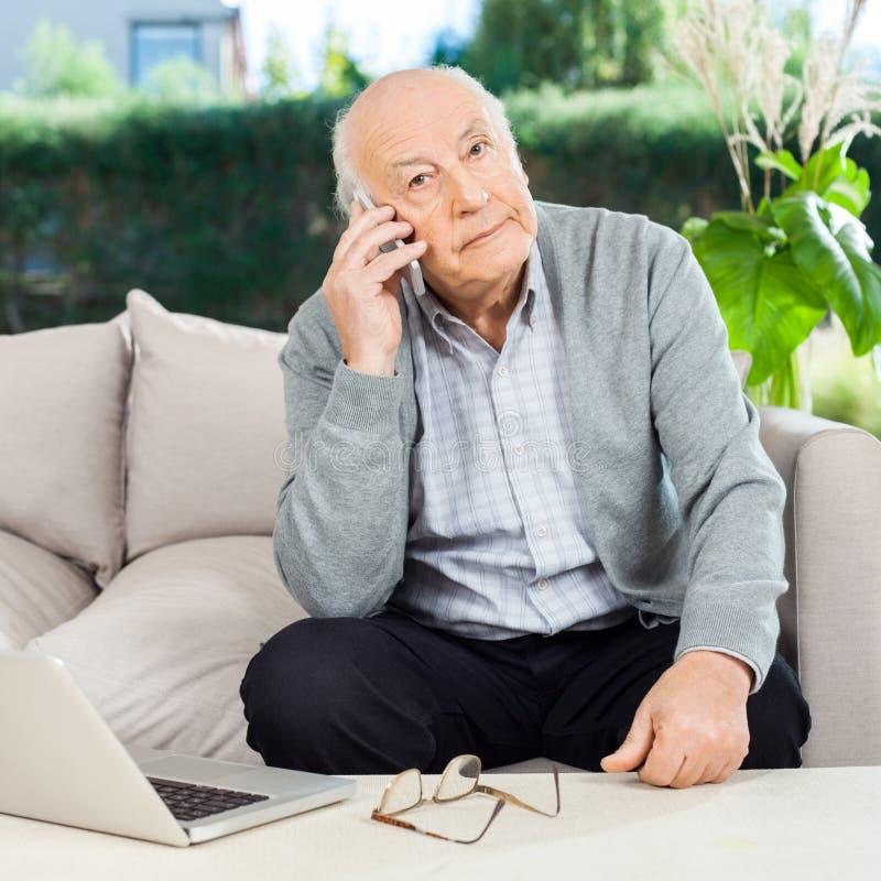 Homem superior que usa Smartphone no patamar do lar de idosos foto de stock