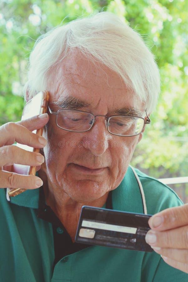 Homem superior que usa um cartão de crédito sobre o telefone imagens de stock royalty free