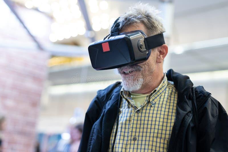 Homem superior que veste os óculos de proteção da realidade virtual que olham a apresentação da realidade virtual fotografia de stock
