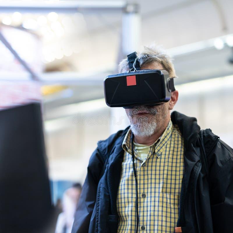 Homem superior que veste os óculos de proteção da realidade virtual que olham a apresentação da realidade virtual fotografia de stock royalty free