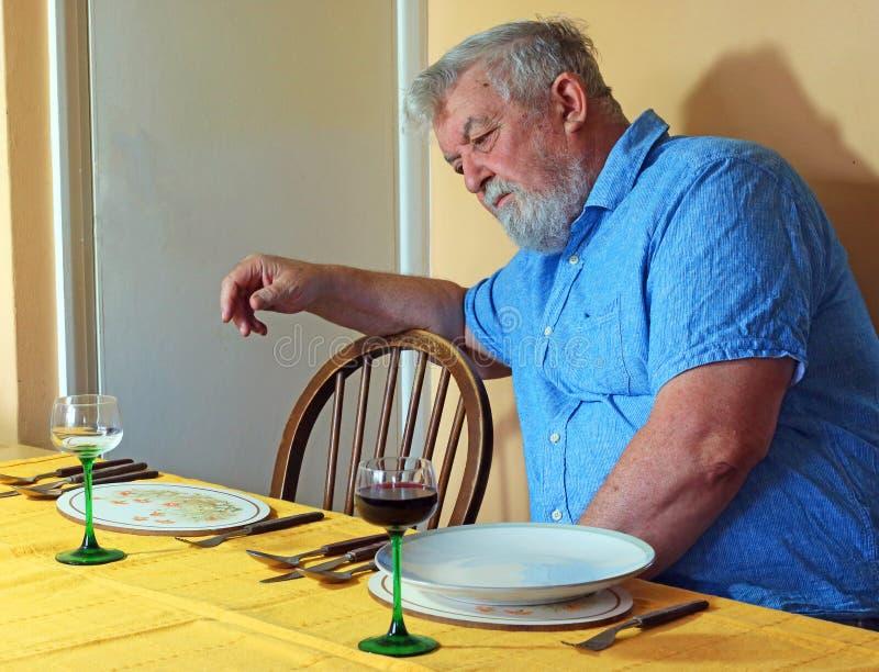 Homem superior só na tabela de jantar imagens de stock