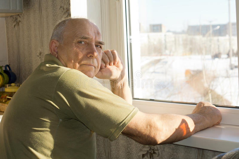 Homem superior só que senta-se em uma janela imagens de stock