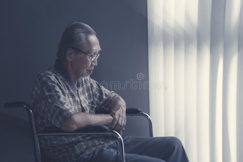 Homem superior solitário que senta-se na cadeira de rodas foto de stock