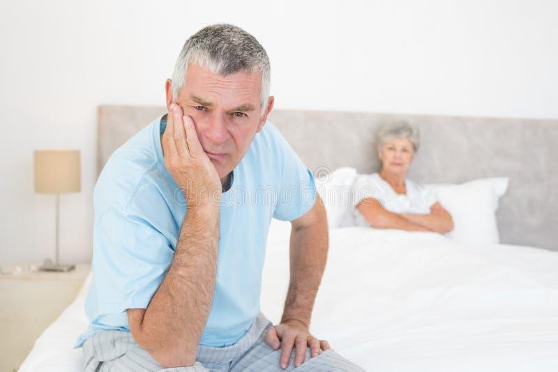 Homem superior triste com a mulher na cama fotografia de stock